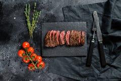Grilled roasting rare sliced skirt, machete steak. Marble meat beef. Black background. Top view