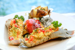 Grilled rock lobster skillet with baked potatoes. Grilled rock lobster with baked potato Royalty Free Stock Photos