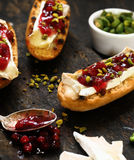 Grilled roll topped with camembert and cranberries Stock Image