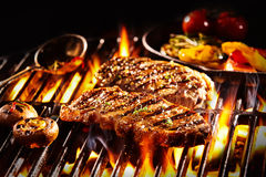 Grilled rump steak with mushrooms over flames. Grilled pieces of delicious rump steak garnished with herbs and sauce alongside mushrooms and vegetables over Royalty Free Stock Images