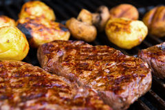 Grilled rump steak with mushrooms and potatoes on barbecue Royalty Free Stock Photo