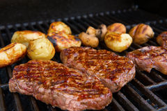 Grilled rump steak with mushrooms and potatoes on barbecue Stock Photography