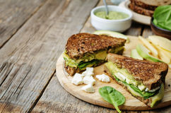Grilled rye sandwiches with cheese, spinach, pesto, avocado and Royalty Free Stock Photos