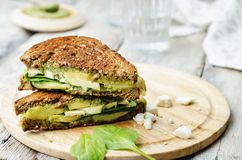 Grilled rye sandwiches with cheese, spinach, pesto, avocado and Stock Photography