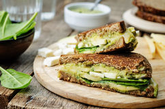 Grilled rye sandwiches with cheese, spinach, pesto, avocado and Stock Images