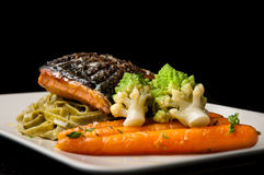 Grilled salmon. With pasta, romanesco broccoli and glazed carrots Royalty Free Stock Image