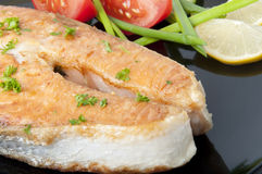 Grilled salmon. A delicious salmon steak with vegetables Royalty Free Stock Photos