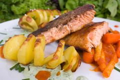 Grilled salmon. With asparagus in paprika chutney and potato spirals royalty free stock photos
