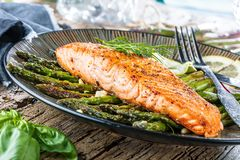 Grilled salmon and asparagus on wooden table close up stock photo