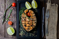 Grilled salmon on black board. On wooden background Stock Images