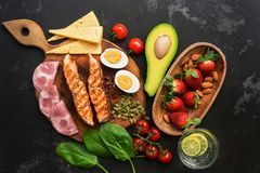 Grilled salmon with boiled egg, ham, vegetables and strawberries on a dark background. Ketogenic dietary dinner or lunch. Top view. Flat lay stock photography