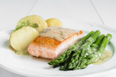 Grilled salmon with boiled potatoes and asparagus on white plate Stock Image