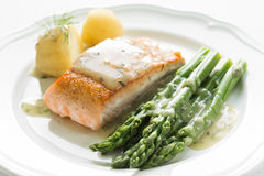 Grilled salmon with boiled potatoes and asparagus on white plate Stock Photo