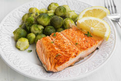 Grilled salmon with brussels sprouts garnish and lemon Royalty Free Stock Image