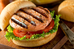 Grilled Salmon Burger. A delicious homemade grilled salmon burger with tomato and lettuce on a bun Stock Image