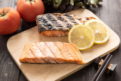Grilled salmon on cutting board on wooden background. Stock Photos