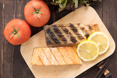Grilled salmon on cutting board on wooden background Stock Photo