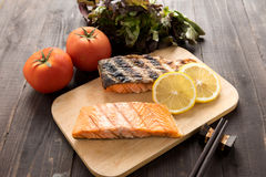 Grilled salmon on cutting board on wooden background royalty free stock images