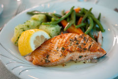 Grilled Salmon Dish. A thick cut of broiled salmon presented on a white plate. It is plated next to potato, lemon slices and a boiled vegetables stock photos