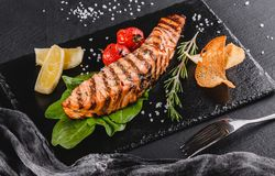 Grilled salmon fillet garnished with spinach, lemon, herbs on plate over wooden background. Hot fish dish.  stock photo