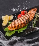 Grilled salmon fillet garnished with spinach, lemon, herbs on plate over wooden background. Hot fish dish.  stock images