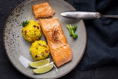 Grilled Salmon Fillet with Saffron Risotto. On Dark Background royalty free stock photography