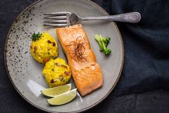 Grilled Salmon Fillet with Saffron Risotto. On Dark Background royalty free stock images