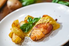 Grilled salmon fillet wrapped in bacon and potato wedges on white plate. Close up royalty free stock photo