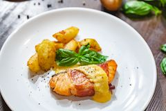Grilled salmon fillet wrapped in bacon and potato wedges on white plate. Close up stock photo