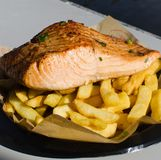 Grilled salmon fish with chips on a black plastic plate. A Grilled salmon fish with chips on a black plastic plate stock image