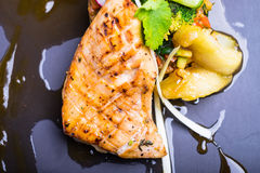 Grilled salmon fish fillet with fresh tomatoes, radish, cucumbers on a plate Royalty Free Stock Images