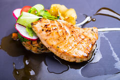 Grilled salmon fish fillet with fresh tomatoes, radish, cucumbers on a plate Stock Photos