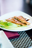 Grilled salmon fish with salad on a white plate Royalty Free Stock Image