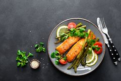 Grilled salmon fish steak, asparagus, tomato and corn salad on plate. Healthy dish for lunch. Top view stock image