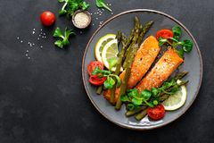 Grilled salmon fish steak, asparagus, tomato and corn salad on plate. Healthy dish for lunch. Top view stock photography