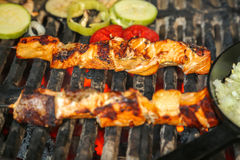 Grilled salmon. On the flaming grill with vegetablesn royalty free stock images