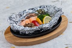 Grilled Salmon in a Foil Pack with broccoli, bell pepper, mushroom and slice lemon served in hot plate on wooden plate on washi. Grilled Salmon in a Foil Pack Royalty Free Stock Photos