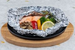 Grilled Salmon in a Foil Pack with broccoli, bell pepper, mushroom and slice lemon served in hot plate on wooden plate on washi. Grilled Salmon in a Foil Pack Stock Photo