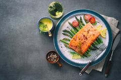 Grilled salmon garnished with green asparagus and tomatoes Stock Images