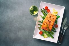 Grilled salmon garnished with green asparagus and tomatoes Stock Photos