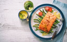 Grilled salmon garnished with green asparagus and tomatoes Royalty Free Stock Photo