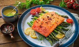 Grilled salmon garnished with green asparagus and tomatoes. Top view Royalty Free Stock Photo