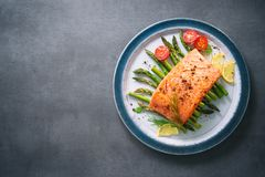 Grilled salmon garnished with green asparagus and tomatoes Royalty Free Stock Images