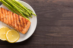 Grilled salmon with lemon, asparagus on the wooden background Royalty Free Stock Photography