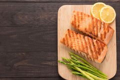 Grilled salmon and lemon, asparagus on the wooden background Royalty Free Stock Photo