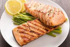 Grilled salmon and lemon, asparagus, on the wooden table Royalty Free Stock Images
