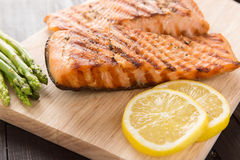 Grilled salmon and lemon, asparagus, on the wooden table Stock Photography