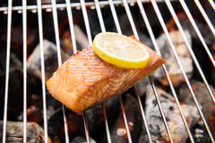 Grilled salmon with lemon on the flaming grill royalty free stock images