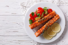 Grilled salmon with lemon and fresh salad on a plate. Horizontal. Grilled salmon with lemon and fresh salad on a plate on the table. Horizontal top view Stock Images