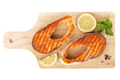 Grilled salmon with lemon slices and herbs on cutting board Stock Image